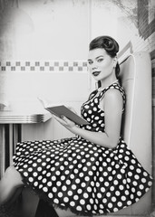 Retro (vintage) portrait of cute young woman sitting in cafe with book. Pin up style portrait of young woman in dress, black and white, texture effect