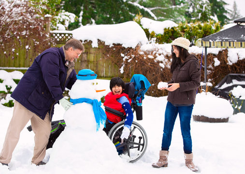 Disabled boy in wheelchair building snowman with family during  winter