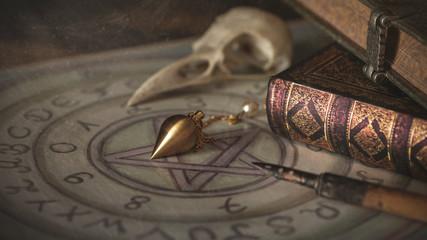 Pendel, Feder, Rabenschädel auf einem Ouijabrett-magische Werkzeuge