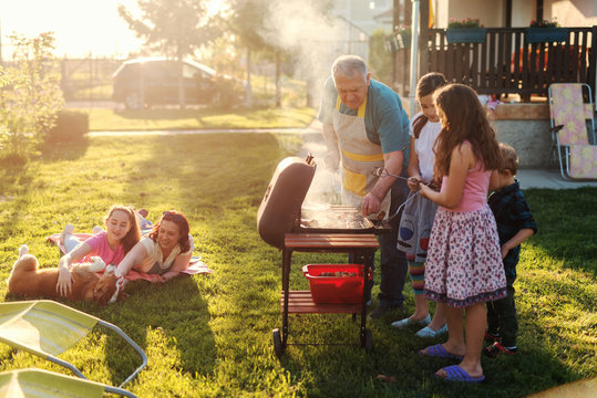 Grandfather teaching his grandchildren how to grill meal. Family gathering in backyard concept.
