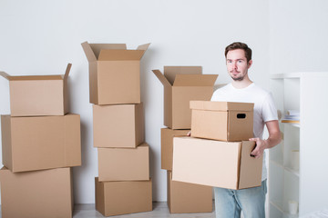 Young man with carton boxes in new apartment.