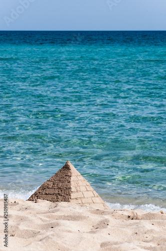 Piramide Di Sabbia Costruita Sulla Spiaggia Con Un Bel Mare Azzurro
