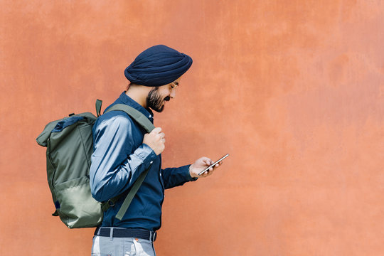Young handsome Indian man holding backpack and typing on his cell phone.