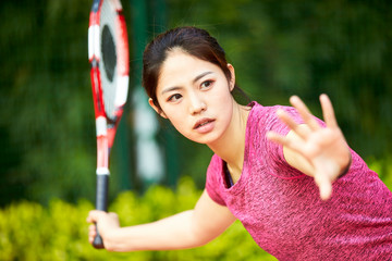 young asian woman playing tennis