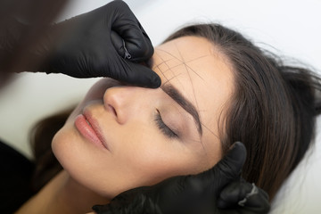 Beautician in the saloon doing the perfect architecture of eyebrows.