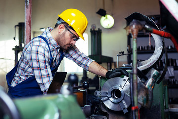 Metal worker turner operating lathe machine at industrial manufacturing factory