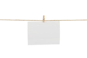 White blank photo card hanging on clothesline.