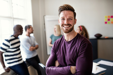 Smiling young designer standing in an office after a presentatio