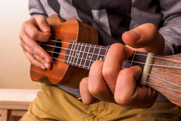 Closeup of young man hands playing acoustic guitar ukulele.