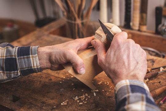 Hände eines Mannes beim Schnitzen auf der Werkbank