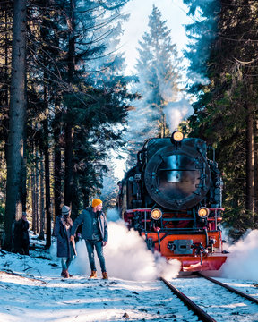 Couple men and woman at Harz steam train during winter in snow landscape, historic steam train in the winter national park Harz Germany