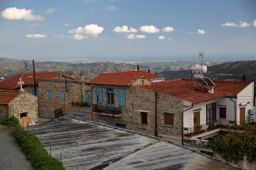 Traditional stony houses with blue shutters and red roofs in lefkara, mountains village in cyprus, hills in background, blue sky with few white clouds