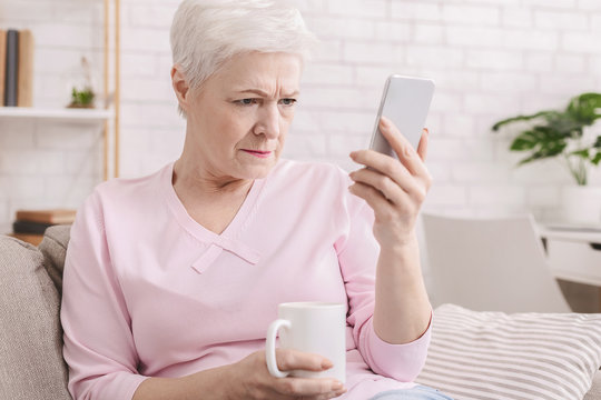 Senior woman with vision problems using phone