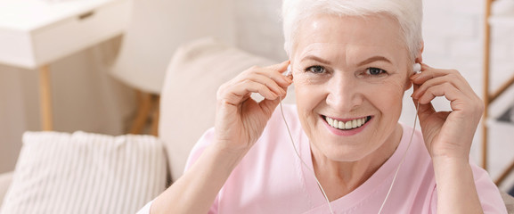 Cheerful aged woman listening to music at home