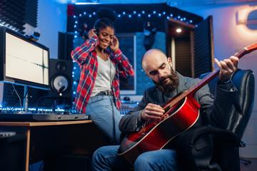 Male and female musicians in recording studio