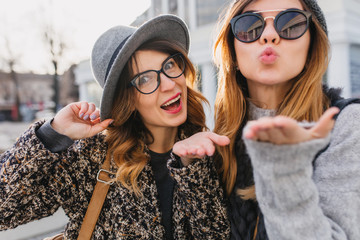 Cute girls wearing elegant glasses sending air kiss while spending time in weekend together. Charming friends having fun outdoor and posing with pleasure, enjoying morning in the city.