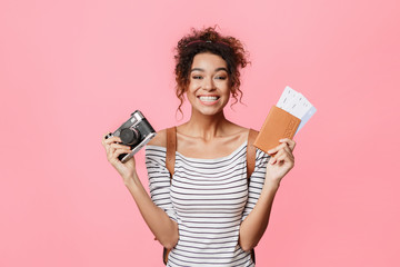 African-american woman holding camera and passport with tickets