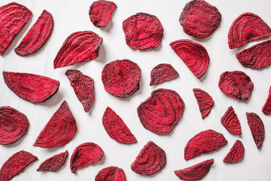 Dried beet chips on a white background, top view.