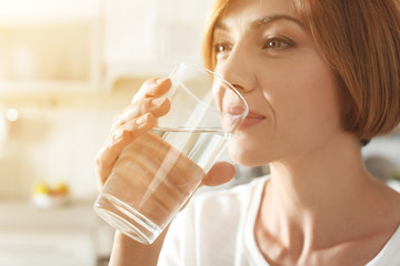 Woman drinking clean water from glass in kitchen, closeup