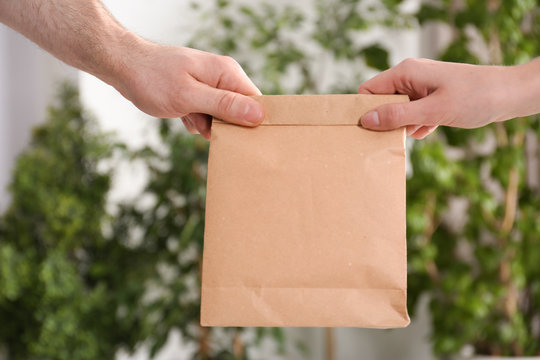 Man giving blank paper bag to woman on blurred background, closeup. Mock up for design