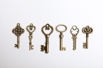 Bronze vintage ornate keys on white background, top view