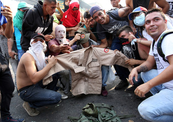 Demonstrators pose for a picture with a Venezuelan man's militia clothes while clashing with security forces in Urena