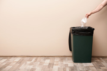 Young woman throwing plastic bottle in trash bin indoors, space for text. Waste recycling