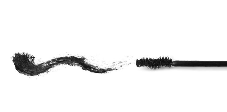 Applicator and black mascara smear for eyelashes on white background, top view