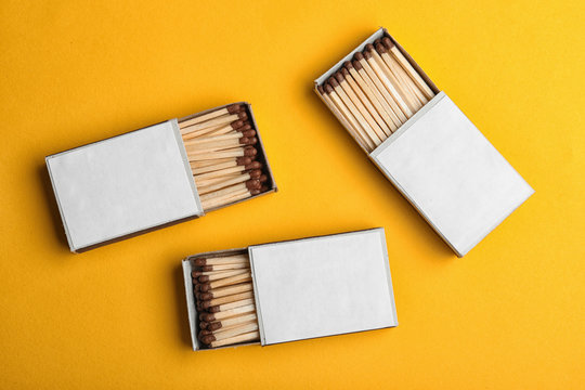 Cardboard boxes with matches on color background, flat lay. Space for design