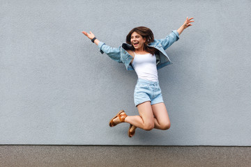 Full length portrait of free happy beautiful woman in casual jeans denim style in summertime jumping at light blue wall, having fun and enjoying.