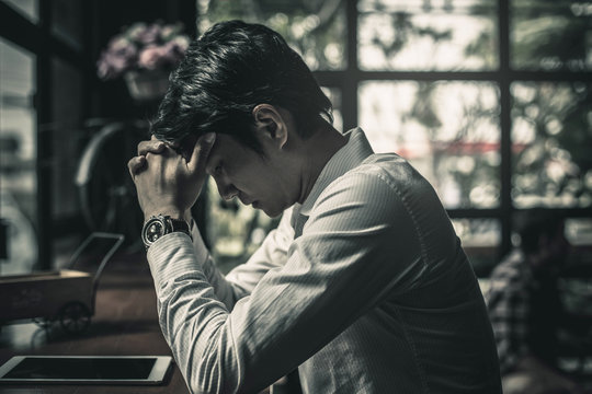 Portrait of an upset businessman at desk in office. Businessman being depressed by working in office.Strain,Yong business man to think and not Work with stress Pretending to put his hand to the head.