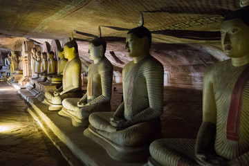many statues of buddha in a cave