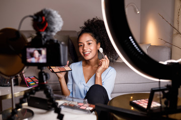 Beauty vlogger making a video tutorial on makeup in living room Wall mural
