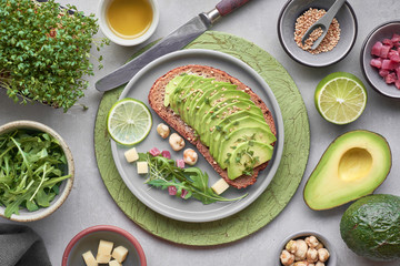 Avocado sandwich and green salad with ham cubes on brown-green textured background