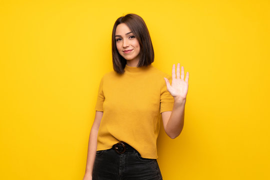 Young woman over yellow wall saluting with hand with happy expression