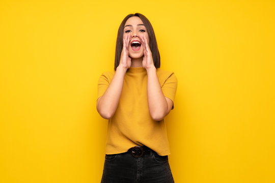 Young woman over yellow wall shouting and announcing something