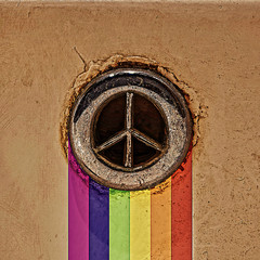 Old rusty peace symbol with rainbow