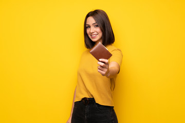 Young woman over yellow wall holding a wallet