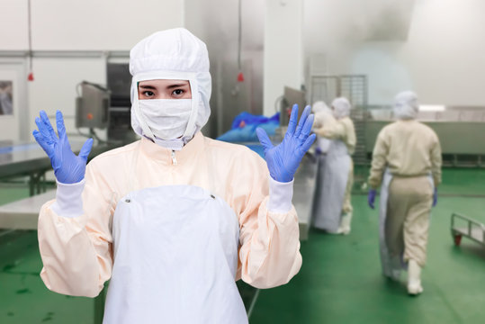 White protective uniform with mask and gloves. Quality control worker jobs in food industrial process.