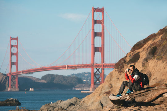 Travel in San Francisco, tourist man with camera in front of Golden Gate Bridge, San Francisco, California, USA