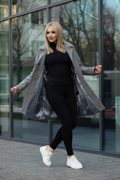 Beautiful young stylish blonde woman wearing coat walking through the city streets. Trendy casual outfit. Street fashion.