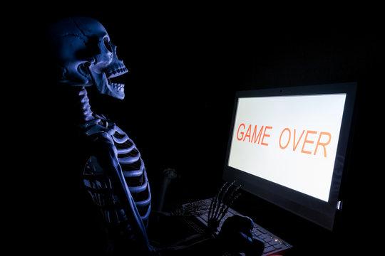 Fake human skeleton sitting in front of desktop computer, computer addicted concept.