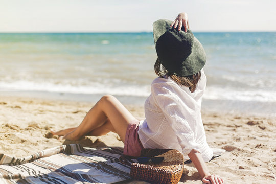 Summer vacation concept. Happy young woman relaxing on beach. Hipster slim girl in white shirt and hat sitting and tanning on beach near sea with waves, sunny warm weather. Peaceful calm moment