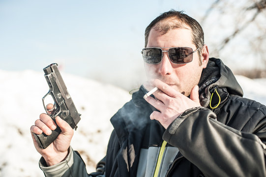 Police agent with gun and cigarette on outdoor shooting range