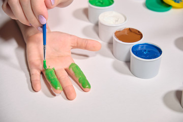 Little girl paints her hands with finger paint on white background