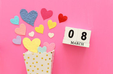 wooden March 8 calendar next to paper colorful hearts over pink wooden background