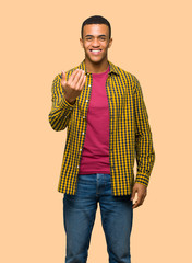 Young afro american man inviting to come with hand. Happy that you came on isolated background