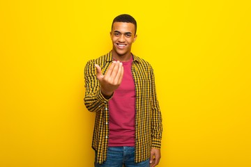 Young afro american man on yellow background inviting to come with hand. Happy that you came