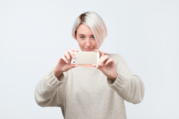 Young european woman in sweater makes photo using phone