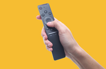 Hand holds tv remote isolated on yellow background